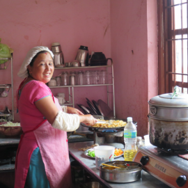 A women of the community preparing traditional food - Women like her will benefit from the grant